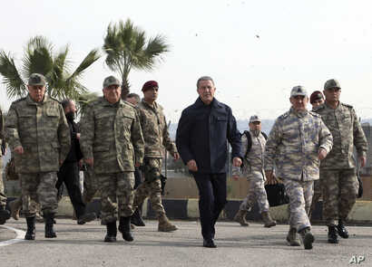 Turkey's National Defence Minister Hulusi Akar, center, and Turkish army's top commanders arrive to inspect troops at the border with Syria, in Hatay, Feb. 3, 2020.