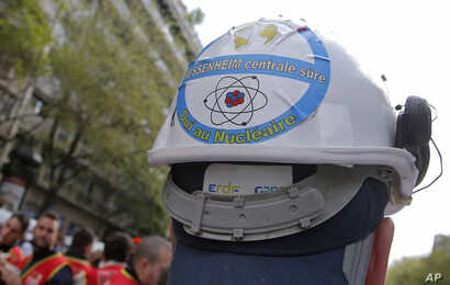 FILE - In this file photo dated Thursday, April 6, 2017, a sticker is photographed on a helmet of an employee of Fessenheim's…