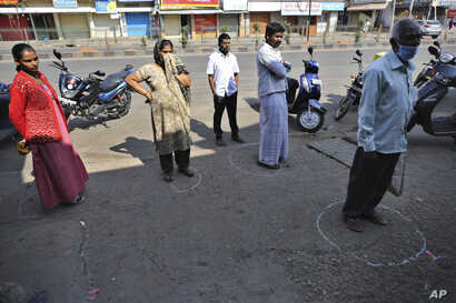 Indians stand in marked positions to maintain physical distance outside a grocery store during lockdown in Bangalore, India,…