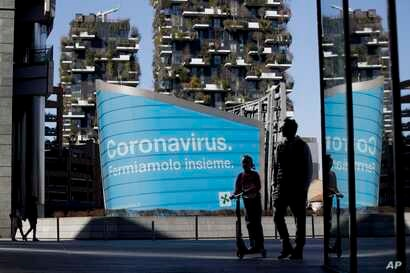 A man and a girl on a scooter are backdropped by a Lombardy region campaign advertising reading in Italian ' Coronavirus let's…