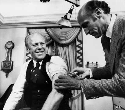 U.S. President Gerald Ford rolls up his sleeve and receives a Swine Flu injection from White House physician, Dr. William…