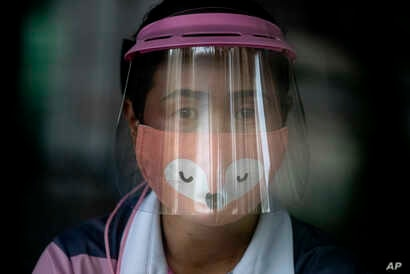 A volunteer wearing a face shield and mask manages a counter of COVID-19 infection screening center at the Chulalongkorn…