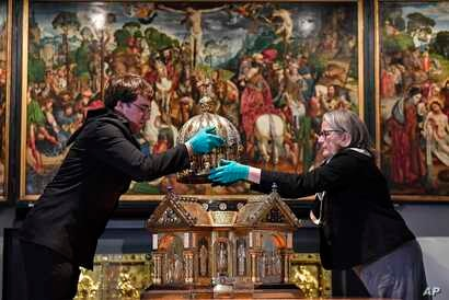 Director Birgitta Falk, right, and conservator Luke Jonathan Koeppe remove the top of the Saint Corona shrine at the Cathedral…