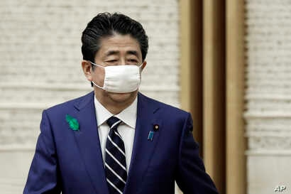 Wearing a protective mask, Japanese Prime Minister Shinzo Abe leaves a news conference at the prime minister's official…