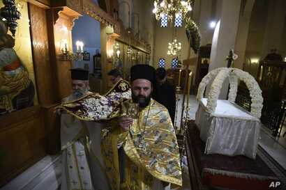 Greek Orthodox priests hold aloft the bier depicting Christ's preparation for burial during the Good Friday procession of the…