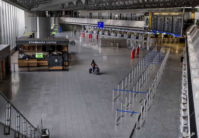 A passenger walks alone at the airport in Frankfurt, Germany, Thursday, April 9, 2020. Due to the coronavirus about 95 percent…