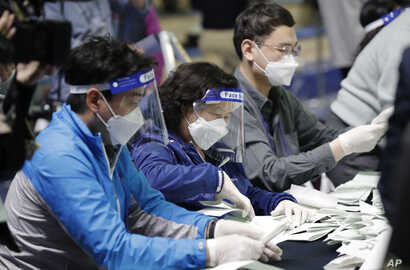 South Korean National Election Commission officials wearing masks and face shields, sort out ballots for counting at the…