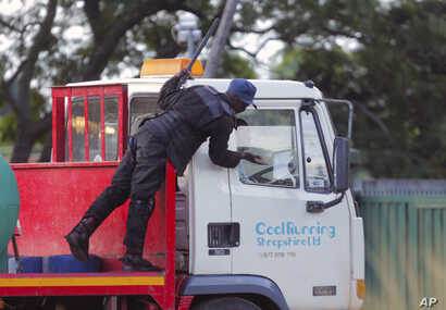 A riot police officer demands a clearance letter to be on the road from a water delivery truck driver, during lockdown due to…