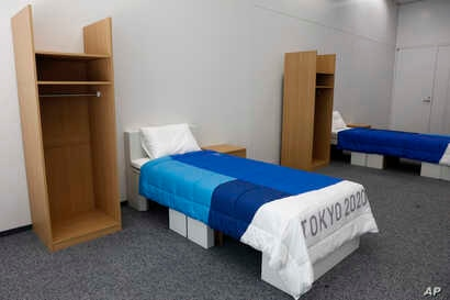Two sets of bedroom furniture, including cardboard beds, for the Tokyo 2020 Olympic and Paralympic Villages are shown in a…