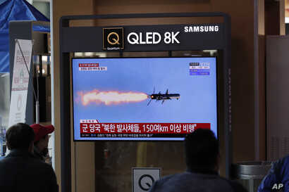 People watch a TV screen showing a news program reporting about North Korea's missiles with a file image at the Seoul Railway…