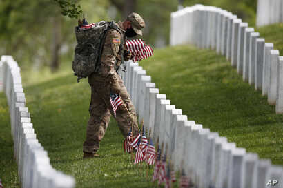 A member of the 3rd U.S. Infantry Regiment also known as The Old Guard, wears a face mask as he places flags in front of each…