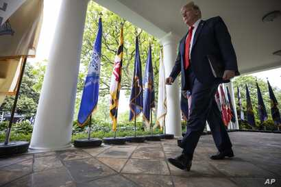 President Donald Trump walks on the colonnade to speak about the coronavirus during a press briefing in the Rose Garden of the…
