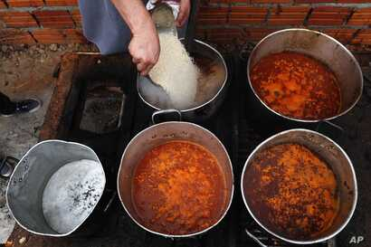 Chef Walter Ferreira pours rice into a stew at a soup kitchen in Luque, Paraguay, Monday, May 11, 2020. The number of soup…
