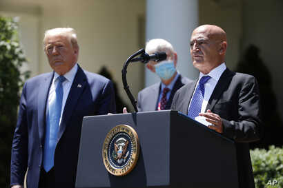President Donald Trump, left, listens as Moncef Slaoui, a former GlaxoSmithKline executive, speaks about the coronavirus in the…