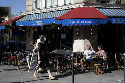 People sit on a terrace in Paris, Tuesday, June 2, 2020. Parisians who have been cooped up for months with take-out food and…