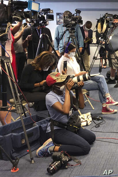 Atlanta Journal-Constitution staff photojournalist Alyssa Pointer, kneeling, works during a news conference, Tuesday, June 2,…