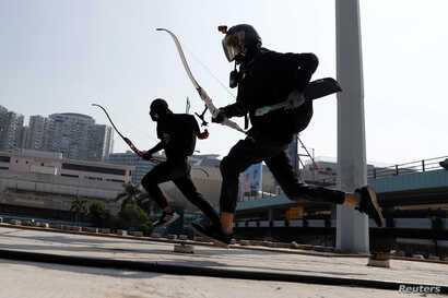 Protesters race with bows as they practice running away from riot police, on the roof of a bus shelter near the Cross Harbour…