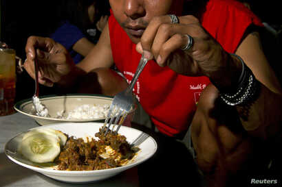 A customer eats dog meat in Yogyakarta May 28, 2011. A meal comprising of dog meat and plain rice costs about 8000 rupiah ($0…