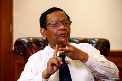 Indonesian Chief Security Minister Mohammad Mahfud MD gestures as he talks during an interview at his office in Jakarta,…