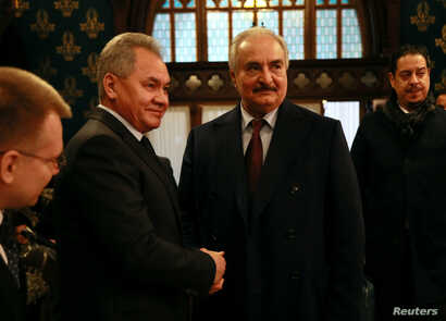 Commander of the Libyan National Army (LNA) Khalifa Haftar shakes hands with Russian Defence Minister Sergei Shoigu before…
