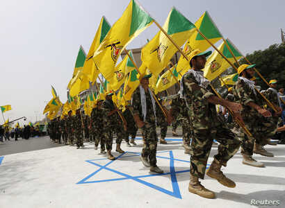 Iraqi Shi'ite Muslim men from the Iranian-backed group Kataib Hezbollah wave the party's flags as they walk along a street…