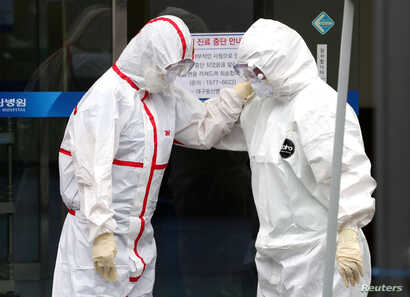 Medical workers wearing protective gears comfort each other outside a hospital in Daegu, South Korea, February 28, 2020.   …