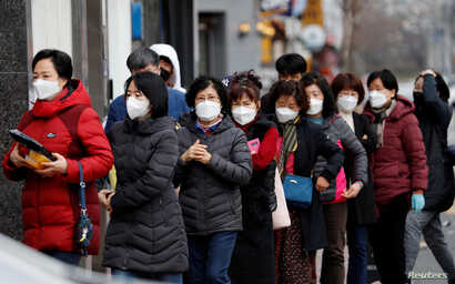People wearing masks stand in a line to buy face masks in front of a drug store amid the rise in confirmed cases of the novel…