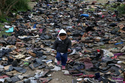 A boy walks among pairs of shoes at the premises of an NGO next to the Moria camp for refugees and migrants, on the island of…