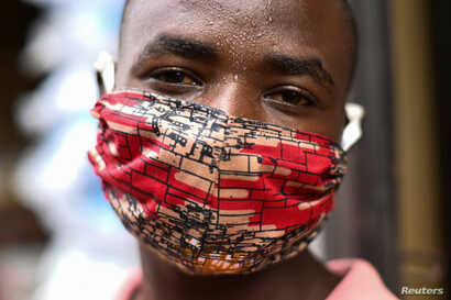 """Pierre Mahiraguha, a vendor at the Kimironko market wears a handmade """"kitenge"""" cloth mask as he attempts to protect against the…"""