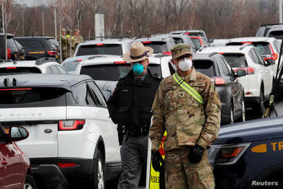 Police and U.S. Military personnel work amid a line of cars of people arriving for testing at a new drive-thru coronavirus…