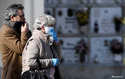 Relatives attend the funeral of a woman who died from coronavirus disease (COVID-19), as Italy struggles to contain the spread…