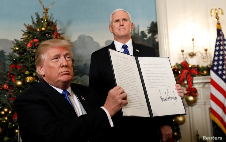 FILE - After signing, U.S. President Donald Trump holds up the proclamation that the United States recognizes Jerusalem as the capital of Israel and will move its embassy there, during an address from the White House in Washington, U.S., Dec. 6, 2017...