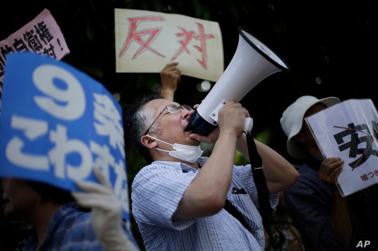 A man shouts slogans over a public-address system during a protest outside the Japanese prime minister's office in anticipation his government will reinterpret the constitution to allow Japan's military a larger international role in Tokyo, Tuesday, ...