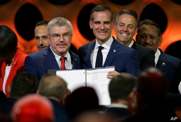 International Olympic Committee President Thomas Bach (IOC), left, poses with Los Angeles Mayor Eric Garrett at the end of an IOC session in Lima, Peru, Sept. 13, 2017.
