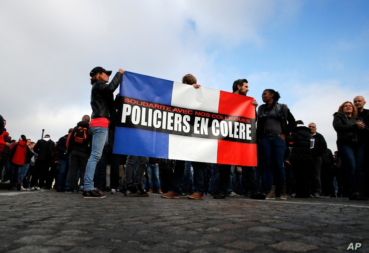 """Police officers hold a French flag reading """"Angry Policemen"""" during a demonstration in front of the National Assembly, in Paris, France, Oct. 26, 2016."""