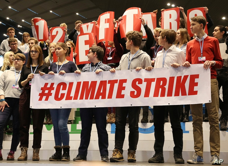 Polish teenagers stage a protest in the U.N. climate conference venue on the last days of talks to urge negotiators from almost 200 countries to reach an agreement on ways of keeping global warming in check, in Katowice, Poland, Dec. 14, 2018.
