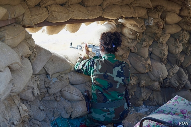 Masuma, 28, an Iranian Kurd volunteer, stands guard observing IS fighters nearby, Nov. 2, 2016. Her brother is fighting alongside her. Before enlisting to fight, they were mule smugglers in Iran. (J. Dettmer/VOA)