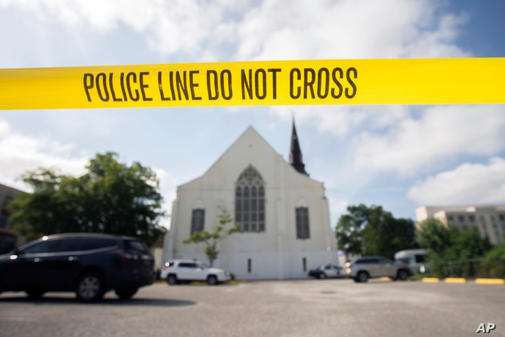 Police tape surrounds the parking lot behind the Emanuel AME Church as FBI forensic experts work the crime scene, June 19, 2015.
