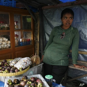Jumilah lost five cattle from the volcanic eruption of Mount Merapi. She is slowly rebuilding her life by selling fruits at a roadside stall.