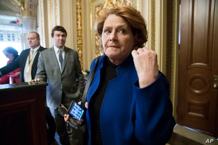 FILE - In this Jan. 22, 2018 file photo, Sen. Heidi Heitkamp, D-N.D., leaves a meeting with fellow Democrats at the Capitol in Washington. l