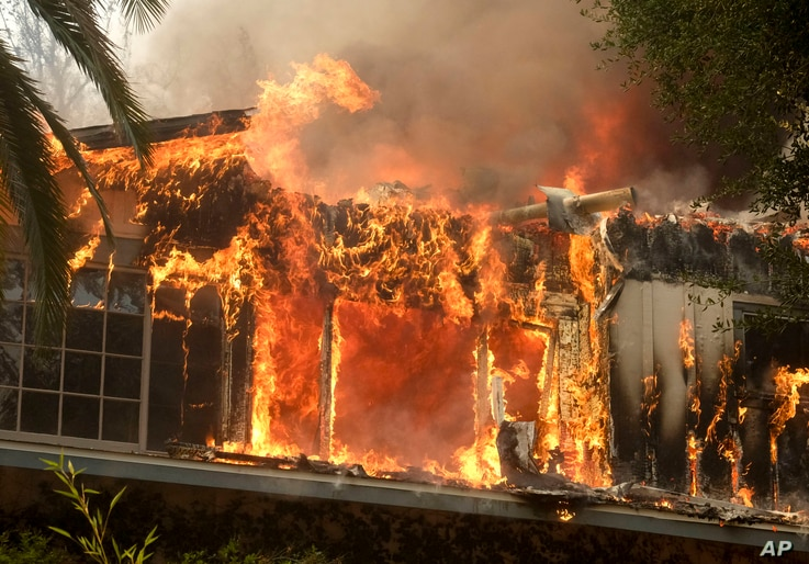 FILE - The Woolsey Fire burns a home near Malibu Lake in Malibu, Calif., Nov. 9, 2018. The fast-moving flames the total evacuation of the celebrity enclave.