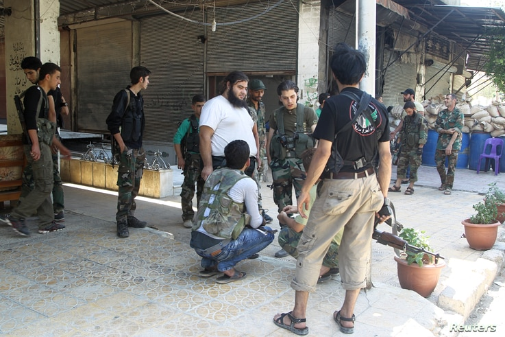 FILE - Free Syrian Army fighters carry their weapons as they gather for what they said was an operation to travel to the northern countryside of Aleppo to fight Islamic State fighters, in Aleppo, Syria.