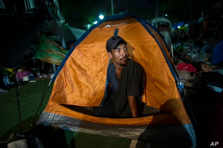 """Joel Eduardo Espinar looks out from his family's tent in the main square of Arriaga, Mexico, Oct. 26, 2018. His plan is to request asylum rather than cross the border illegally. """"I'm kind of fearful of what will happen once we get to the U.S. bor..."""