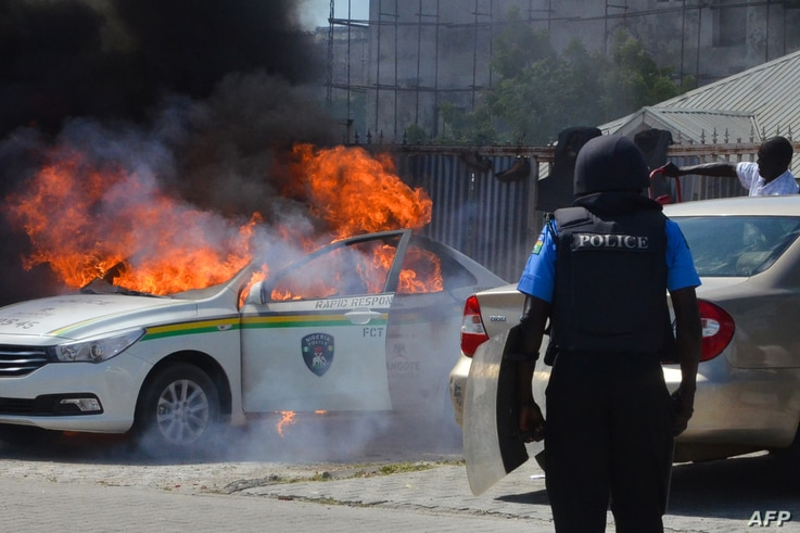 A Nigerian police officers watches a police vehicle as it goes up in flames following clashes with supporters of Islamic Movement of Nigeria (IMN) protesting against the imprisonment of their leader Ibrahim Zakzaky, in Abuja, on Oct. 30, 2018.