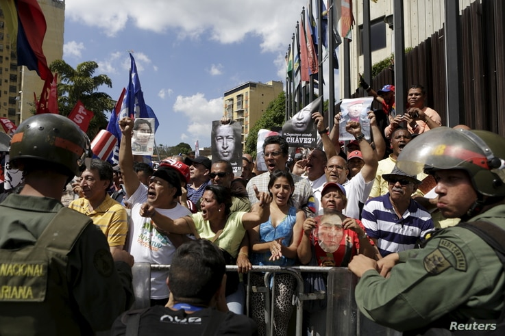 Supporters of Venezuela's President Nicolas Maduro hold up photographs of Venezuela's late President Hugo Chavez as they gather Jan. 7, 2016, outside Supreme Court building in Caracas.