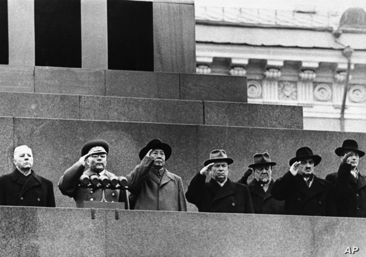 Red China's Mao Tse-Tung (third from left) stands with  top Russian leaders to salute from Lenin Mausoleum  as parade passes below on Nov.11,1957 in Red Square at Moscow.