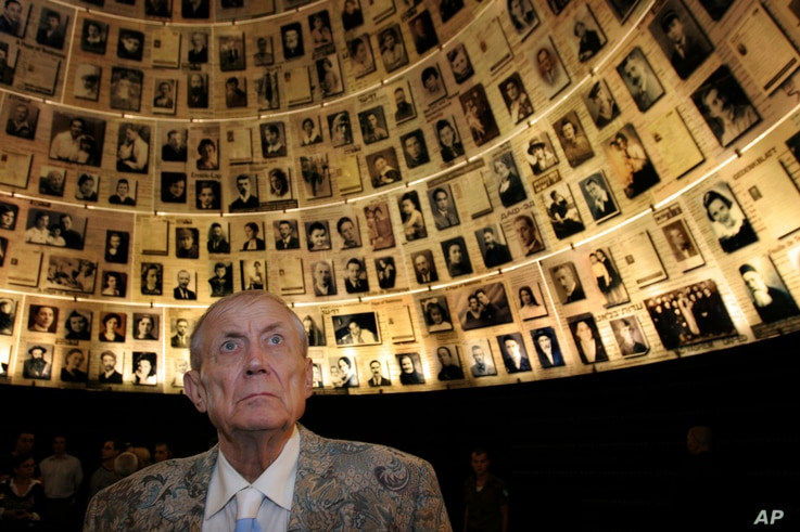 """FILE - Poet Yevgeny Yevtushenko looks at photographs of Jewish Holocaust victims during a visit to the Yad Vashem Holocaust Memorial in Jerusalem, Nov. 15, 2007.  During his visit, Yevtushenko read the poem """"Babi Yar,"""" a poem against anti-Semitism he..."""