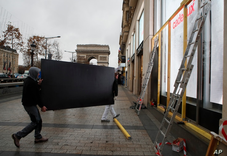 Workers carry a wooden piece to protect shop windows on the Champs-Elysees avenue, Dec. 7, 2018 in Paris.