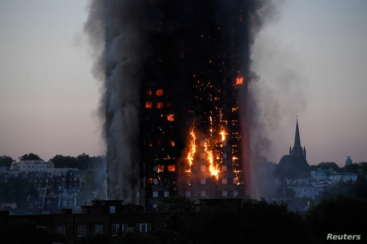 Flames and smoke billow as firefighters deal with a serious fire in a tower block at Latimer Road in West London, Britain, June 14, 2017.