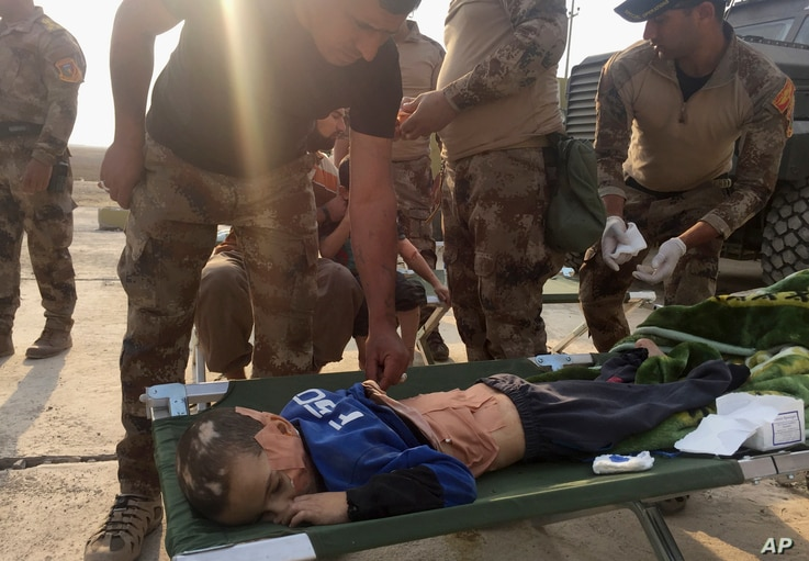Soldiers give the first aid to a boy injured during the clashes between Iraq's elite counterterrorism forces and Islamic State militiants in the village of Tob Zawa, about 9 kilometers (5½ miles) from Mosul, Iraq, Oct. 25, 2016.